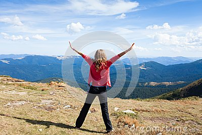 Hiker woman on a peak mountain with raised hands