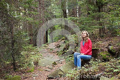 Hiker woman sitting on a halt in the forest