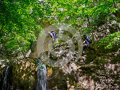 Hikers climb the rocks near the waterfall