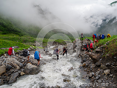 Hikers group cross the mountain river