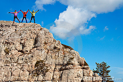 Hikers at the top of a rock with their hands up