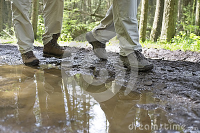 Hikers Walking Through Mud Puddle