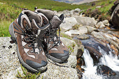 Hiking boots by waterfall in a stream