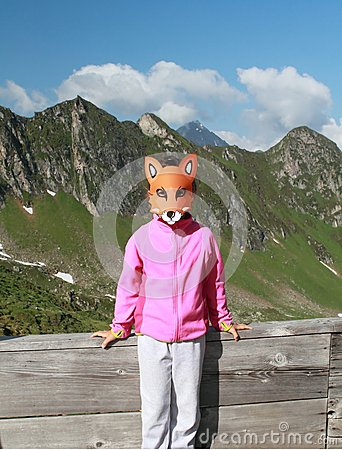 Hiking child with fox mask in the Alps