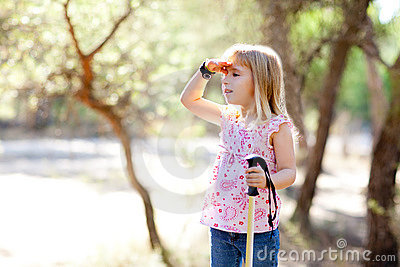 Hiking kid girl searching hand in head in forest