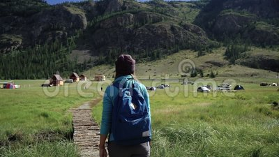 Hiking. Traveler girl with backpack and hat walking on a bridge in the mountains. Camping is in the distance. Adventure. In a hike. Back view, 50 fps stock video