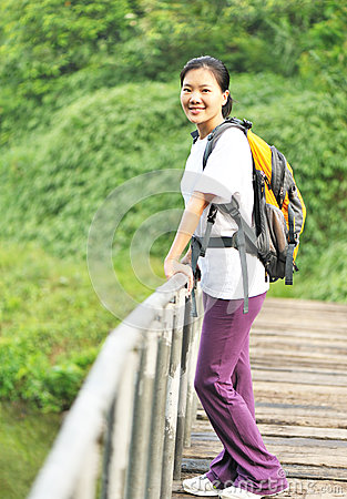 Hiking woman on wooden bridge