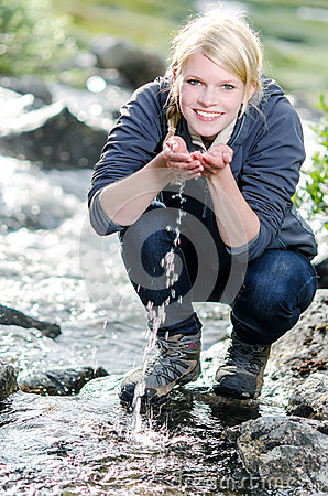 A hiking young blond woman refreshes itself in to a brook
