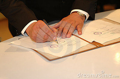Him signing it (Wedding ceremony)