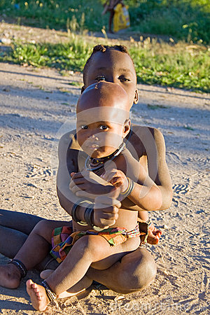 Himba children seat in the sand Editorial Stock Image