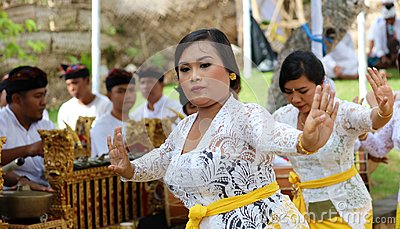 Hindu celebration at Bali Indonesia, religious ceremony with yellow and white colors, woman dancing. Editorial Stock Photo