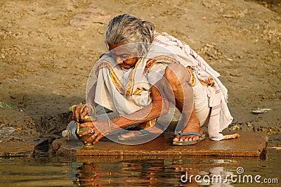 Hindu Pilgrim cleaning prayer utensil Editorial Stock Photo