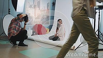 Hinter den Szenen auf der Fotosession: Schwarzes Modell posieren auf dem Boden für Modemagazin fotografieren stock video footage