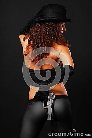 Hintere Ansicht des reizvollen Gangsters eine Pistole versteckend.