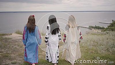 Hintere Ansicht von drei Freundinnen in den schönen langen Sommerkleidern mit Stickerei gehend in Richtung zum Fluss Konzept von stock video footage