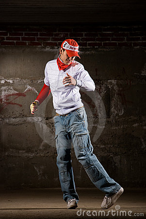 Hip hop boy dancing in modern style over grey wall
