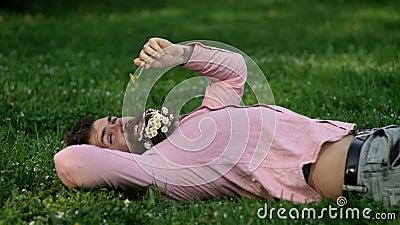 Hippie, der im grünen Gras mit Löwenzahn am sonnigen Tag liegt Hand mit Armbanduhr in eine Tasche Kerl mit Kamille im entspannend stock footage
