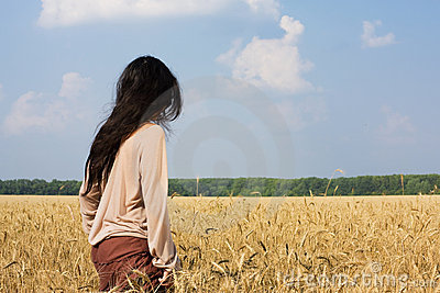 Hippie girl in wheat field rear view