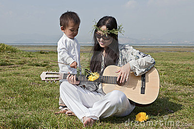 Hippie mother playing guitar with son