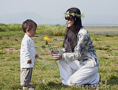 Hippie woman gives son a yellow flower
