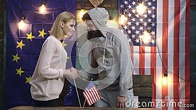 Hippies Frau und das Mannrütteln überreicht Amerikaner- und EU-Flaggen H?ndedruck ?ber Amerikaner- und EU-Flaggen mitarbeit stock video