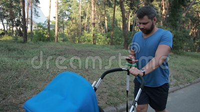 Hipster father with pram walking in public park stock footage