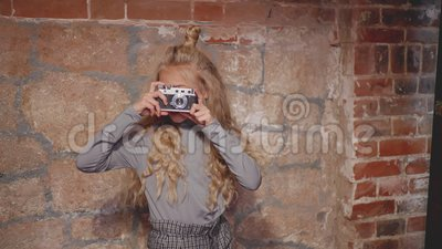 Hipster girl making photography on vintage camera on brick wall background. Young girl using retro photo camera in photo. Hipster girl making photography on stock video footage