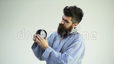 Hipster mit Bart und Schnurrbart verschlafen Mann mit langweiligen, schlaflosen Gesichtern auf der Decke, hält Wecker-Uhr Mensche stock video