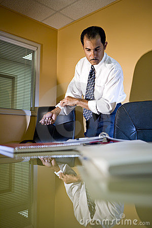 Hispanic businessman in office rolling up sleeves