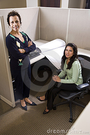 Hispanic businesswomen in cubicle