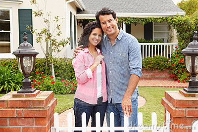 Hispanic couple standing outside new home
