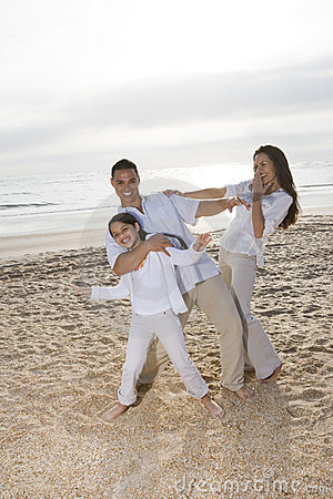 Hispanic family with girl having fun on beach