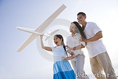 Hispanic family and girl having fun with toy plane