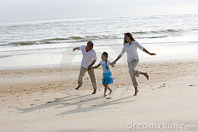 Hispanic family holding hands skipping on beach