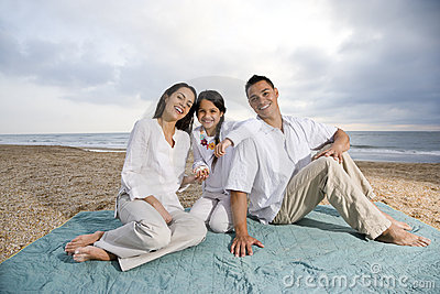 Hispanic family sitting on blanket at beach