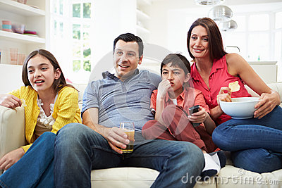 Hispanic Family Sitting On Sofa Watching TV Together