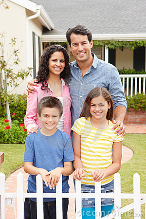 Hispanic family standing outside home