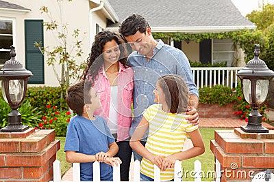 Hispanic family standing outside home