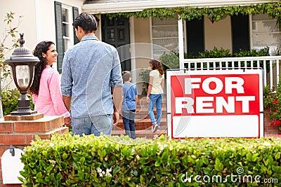 Hispanic family standing outside home for rent