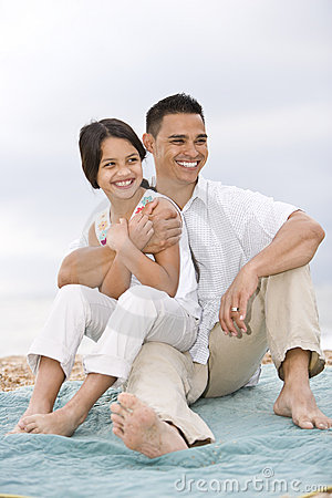 Hispanic father with little girl on beach blanket