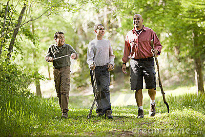 Hispanic father and sons hiking on trail in woods