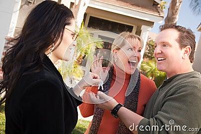 Hispanic Female Real Estate Agent Handing Keys to