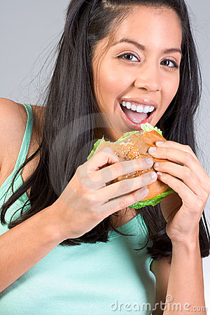 hispanic girl eating burger with lettuce