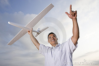 Hispanic man holding model airplane over head