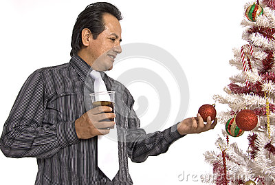 Hispanic man looking at a decorated Christmas Tree