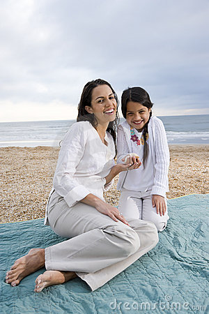 Hispanic mother and girl sitting on beach blanket