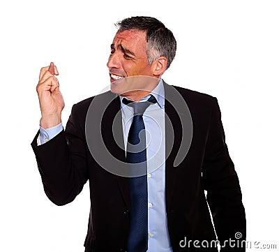 Hispanic senior businessman praying for luck