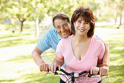 Hispanic senoir couple with bike smiling at camera