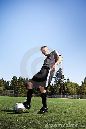 Hispanic soccer or football player kicking a ball