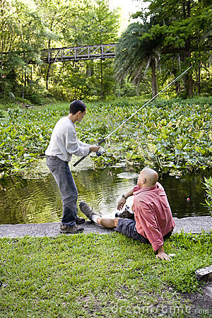 Free Hispanic Teenager And Father Fishing In Pond Stock Photo - 15051370